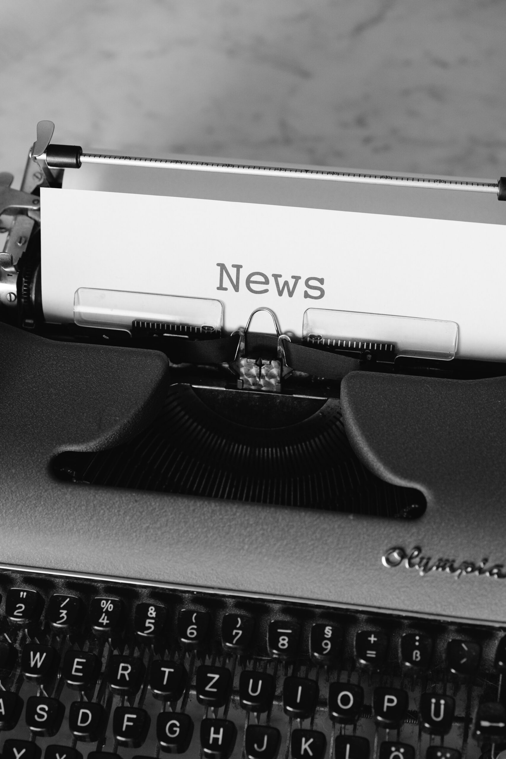"""Decorative image; black & white; a tapewriter with the word """"News"""" written in paper"""
